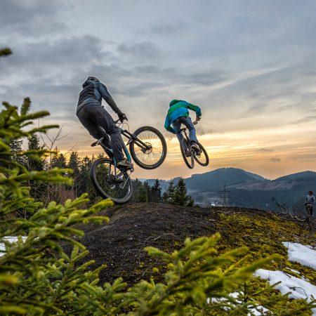 Zwei Mountainbiker springen ueber einen Huegel im Wald.